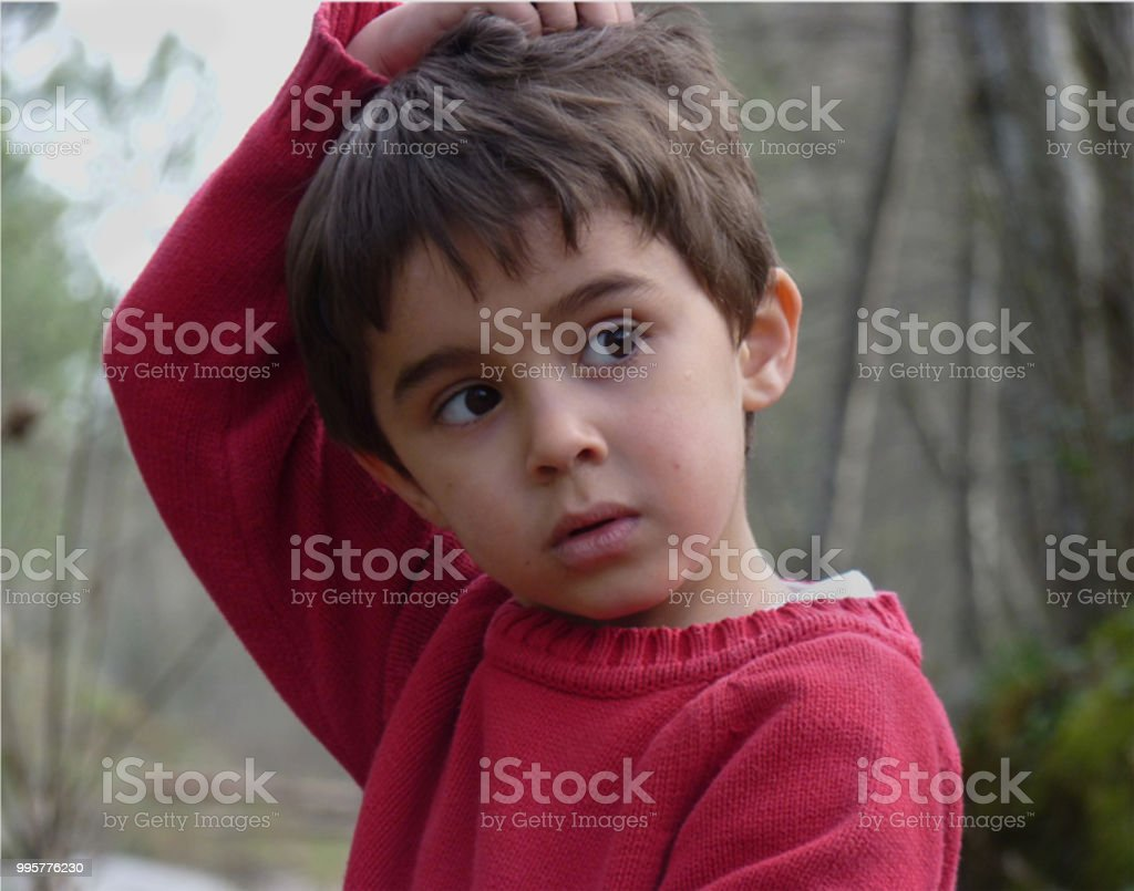 Child with black eyes and red sweater stock photo