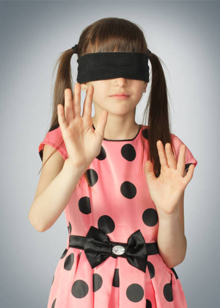 Child with blindfold on grey background stock photo