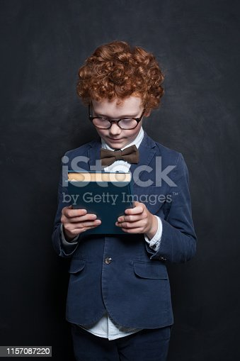 istock Child with book on chalkboard background 1157087220