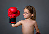 child with boxing gloves, gray background
