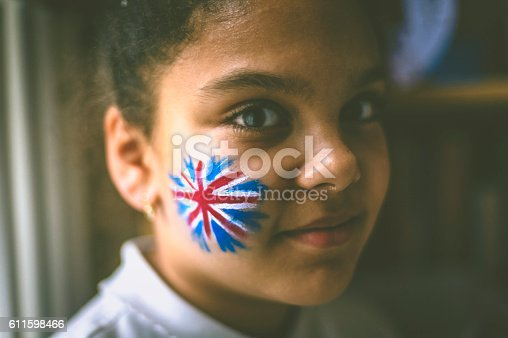 Stock photo of 10 years old girl with a british flag painted on her cheek. This file has a signed model release.