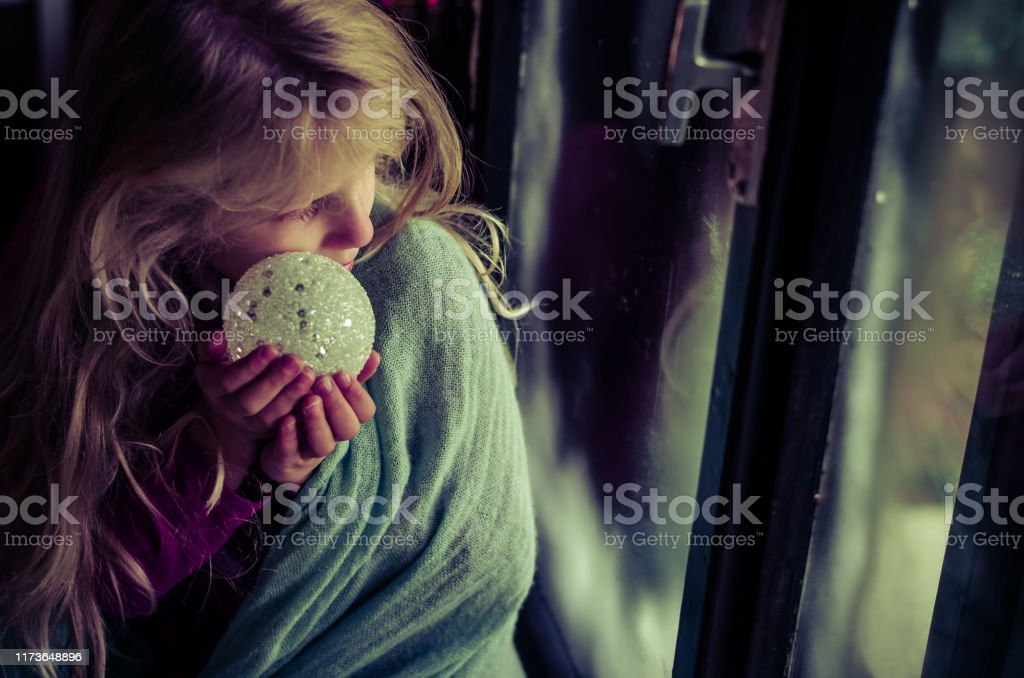 child with christmas bauble looking through window lovely blond girl sitting by the window with christmas bauble and looking from the window Beautiful People Stock Photo