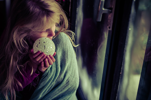 Child With Christmas Bauble Looking Through Window Stock Photo - Download Image Now