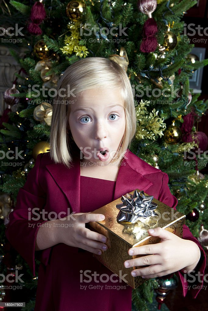 Young girl is excited to open a special Christmas gift. Christmas...