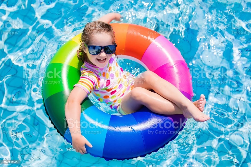 Child with colorful inflatable ring in swimming pool stock photo