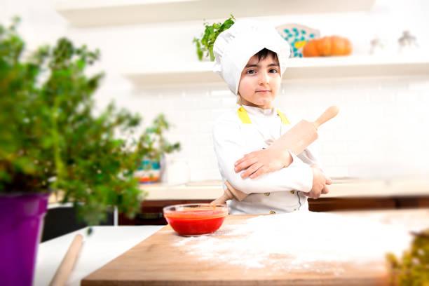 Kind mit gekreuzten Armen als Koch verkleidet – Foto