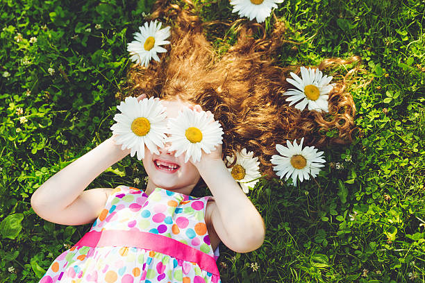 Child with daisy eyes lying on green grass. stock photo
