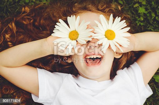 Child with daisy eyes, on green grass in a summer park.