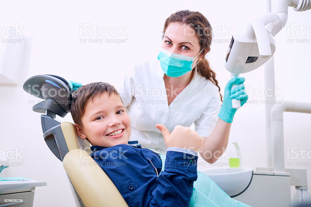 Child with doctor in the office shows thumb stock photo