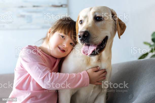 Child with down syndrome embracing labrador retriever and looking at picture id956318250?b=1&k=6&m=956318250&s=612x612&h=wwmdzjtz u95cla1c35jsl5caqbzclqqvkf7muvpipe=