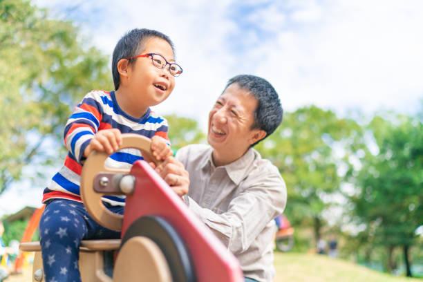 公共公園で父親と一緒に楽しんでいるダウン症の子供 - 障がい ストックフォトと画像