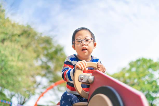 遊び場で遊ぶダウン症候群の子供 - disabilitycollection ストックフォトと画像