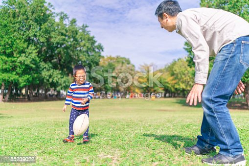 589135214 istock photo Child with down syndrome playing rugby with his father 1185239022