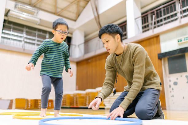 インストラクターと体操を練習するダウン症の子供 - disabilitycollection ストックフォトと画像