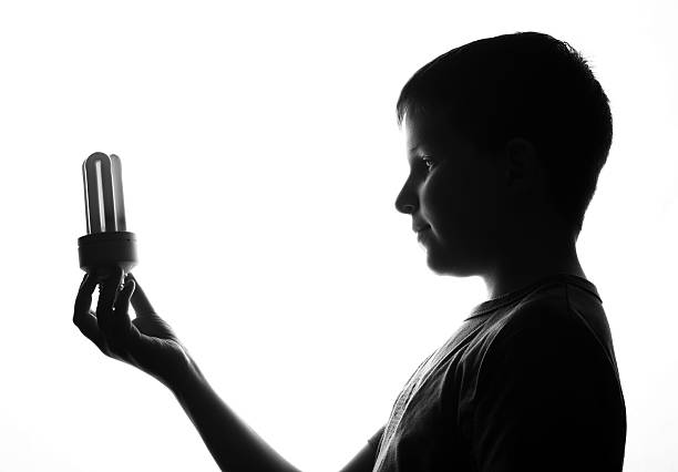 Child with energy saving light bulb stock photo