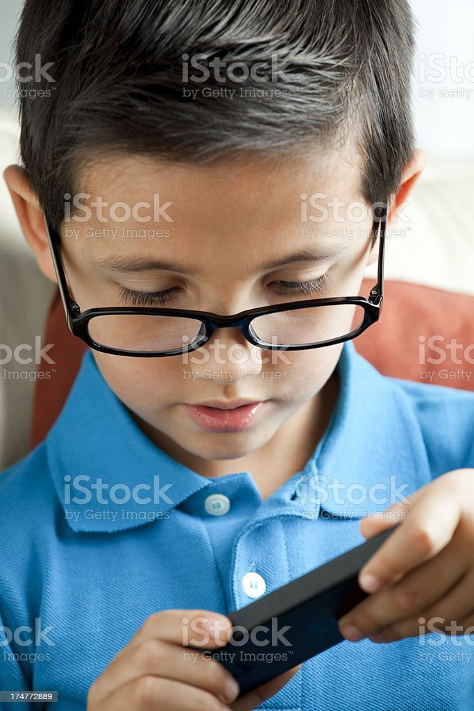 Child with eyeglasses playing on smartphone royalty-free stock photo