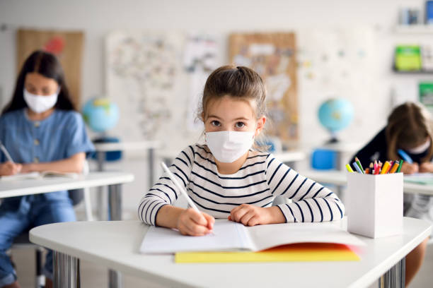 Child with face mask back at school after covid-19 quarantine and lockdown, writing. Front view portrait of child with face mask back at school after covid-19 quarantine and lockdown, writing. {{relatedSearchUrl(carousel.phrase)}} stock pictures, royalty-free photos & images