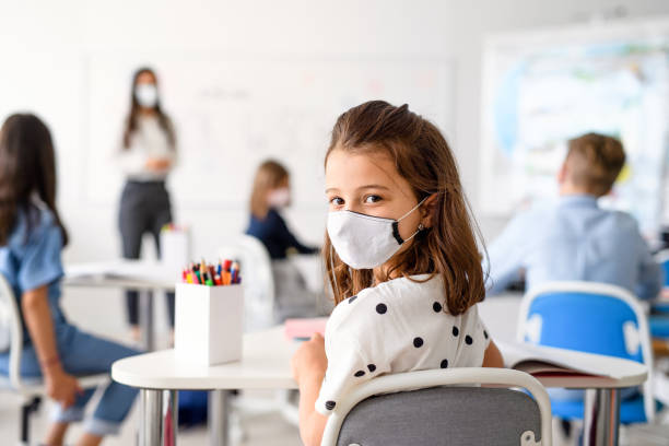 Child with face mask back at school after covid-19 quarantine and lockdown. stock photo