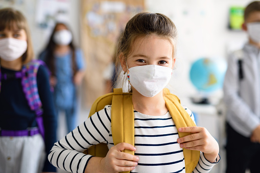 Front view of child with face mask going back to school after covid-19 quarantine and lockdown.