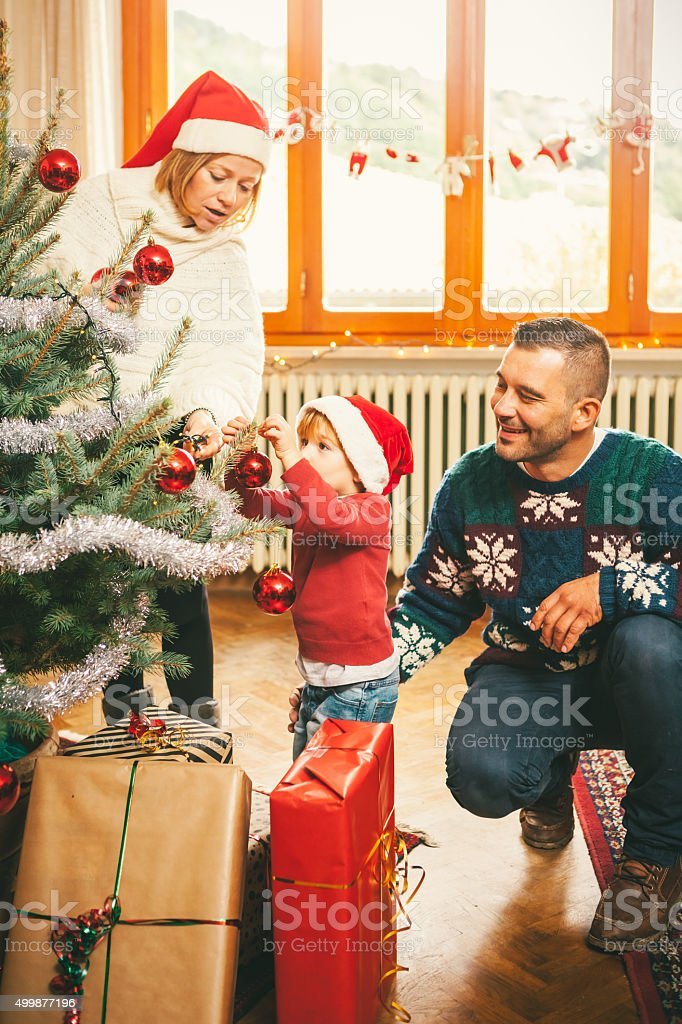 Child with Family Decorating the Christmas Tree stock photo