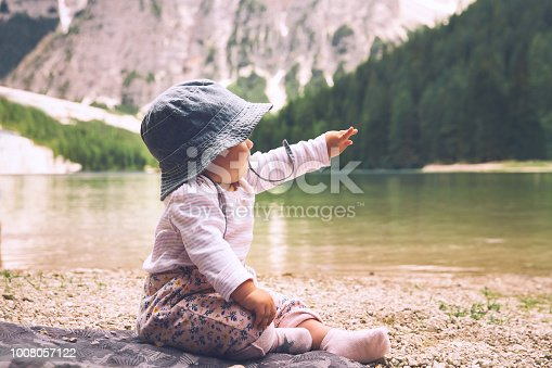 istock Child with family on walk on Braies Lake. Cute baby girl sits on lake shore of Lago di Braies in Dolomites, South Tyrol, Italy 1008057122