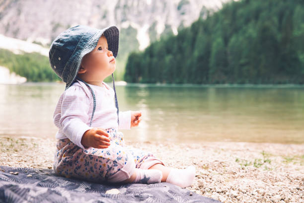 Niño con familia en paseo en el lago de Braies. Niña linda se encuentra en lago orilla de Lago di Braies en Dolomitas, Tirol del sur, Italia - foto de stock