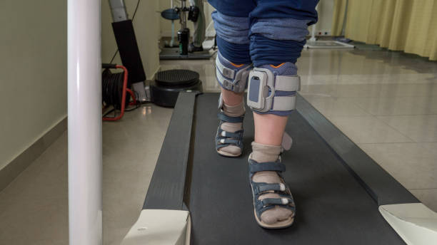 child with foot drop system walking on the treadmill - runner rehab gym foto e immagini stock