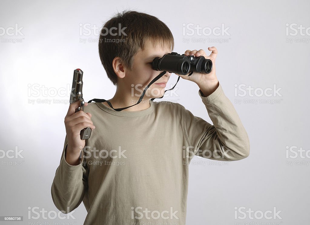 Child with gun and look-see on light background stock photo