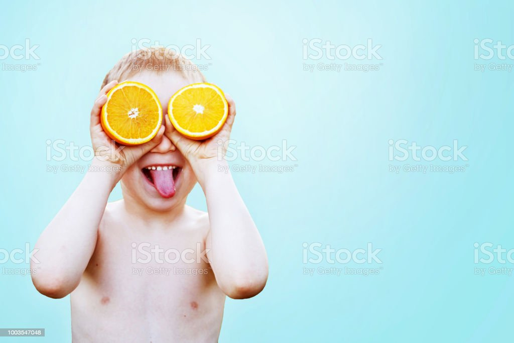 child with halves of oranges on eyes. happy child having fun and...