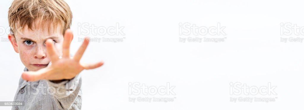 child with hand forwards defending himself or acting bully, banner stock photo