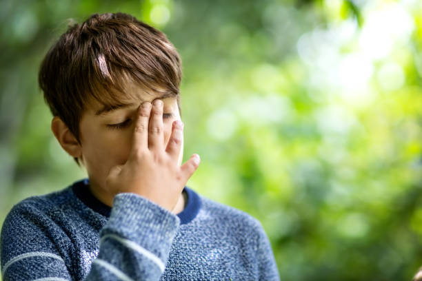Child with headache. Upset young boy outdoors stock photo