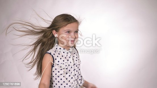 Child with earflaps dancing at studio background. The girl listens to music on the smartphone. The kid has loose long hair. Beautiful cute happy little girl listens to music on Headphones.