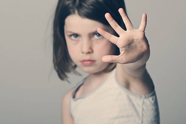 Child with her hand up Powerful shot of a child with her hand up single word no stock pictures, royalty-free photos & images