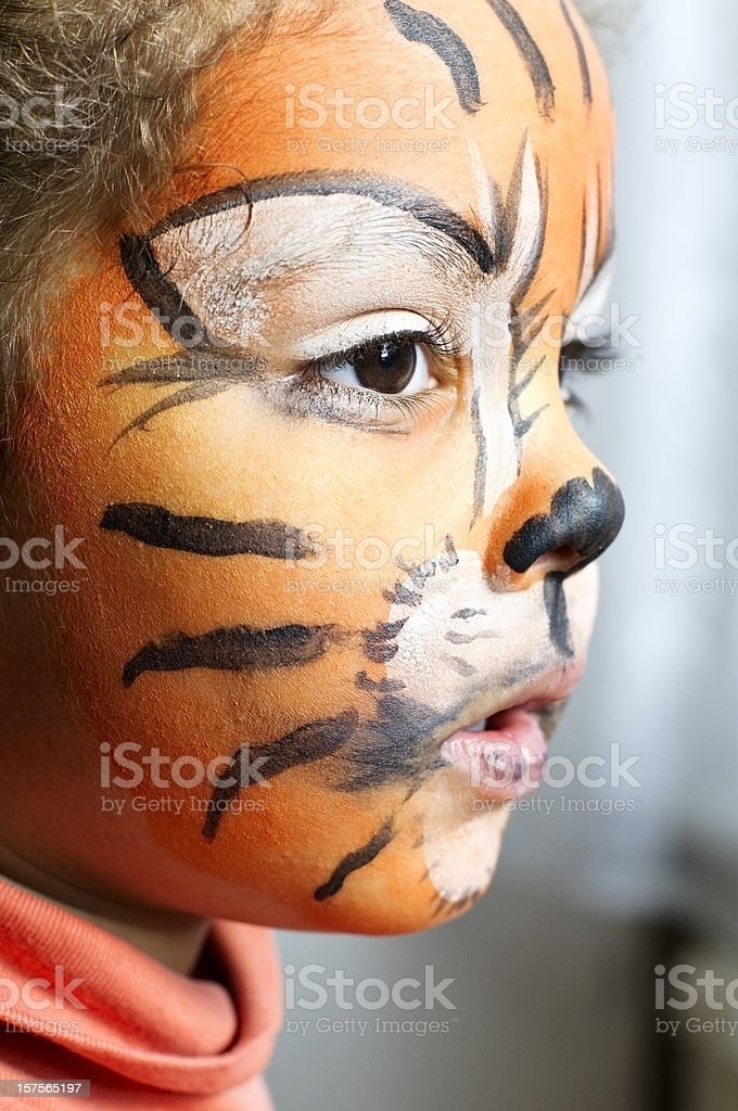 Child with her tiger face paint daydreaming royalty-free stock photo