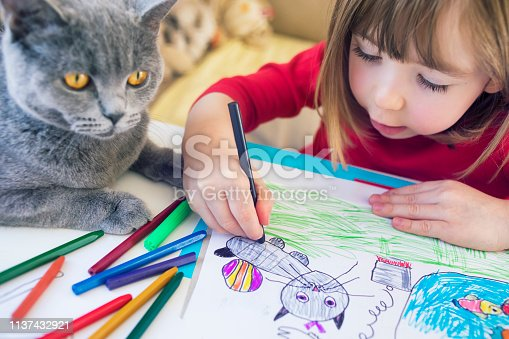 Cute child drawing at home. Kitty next to him.