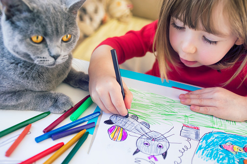 istock Child with kitty drawing at home 1137432921