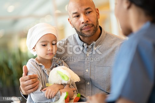 823893962 istock photo Child with leukemia visits the doctor with her father 1153954277