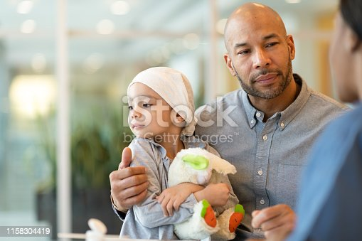 823893962 istock photo Child with leukemia visits the doctor with her father 1158304419