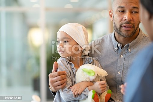 823893962 istock photo Child with leukemia visits the doctor with her father 1162646816