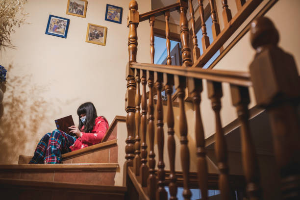 Child with mask reading a book on the stairs. stock photo