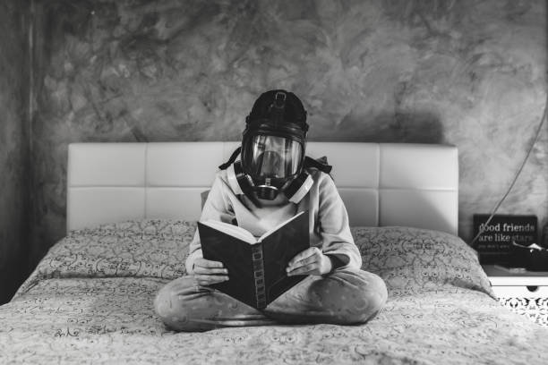 Child with mask reading at home. stock photo