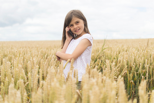 Child with mobile phone in field