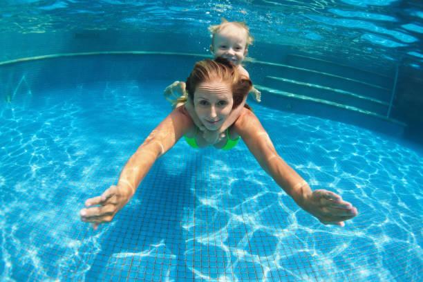 kind mit mutter tauchgang unter wasser im schwimmbad - lustige babybilder stock-fotos und bilder