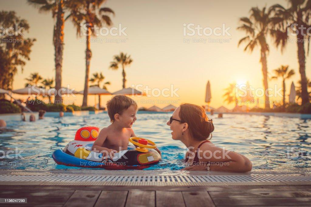 Niño con madre en la piscina, Resort de vacaciones - Foto de stock de Actividades recreativas libre de derechos