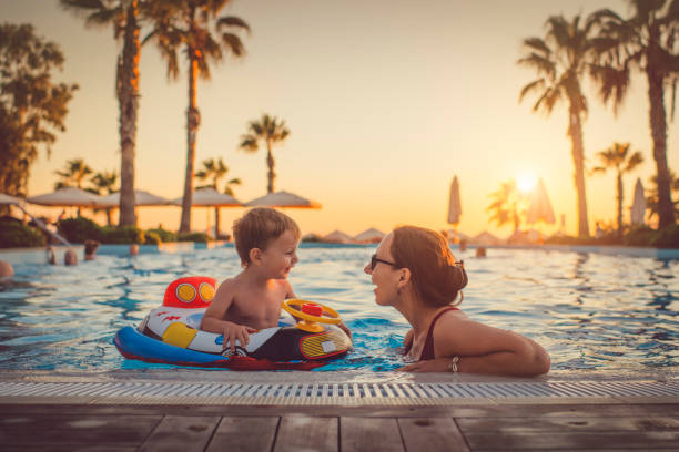 child with mother in swimming pool, holiday resort - vacanze foto e immagini stock