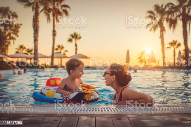 Niño Con Madre En La Piscina Resort De Vacaciones Foto de stock y más banco de imágenes de Actividades recreativas