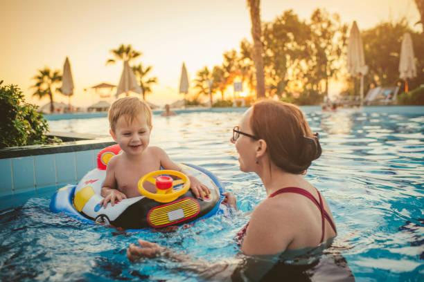 kind mit mutter im schwimmbad, ferienort - 5 sterne hotel türkei stock-fotos und bilder