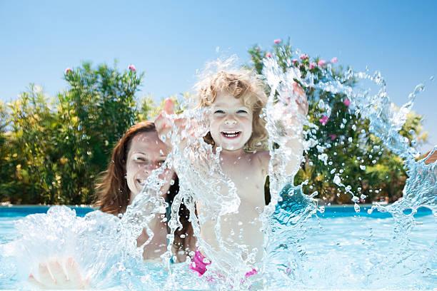 Criança com a mãe na piscina - foto de acervo