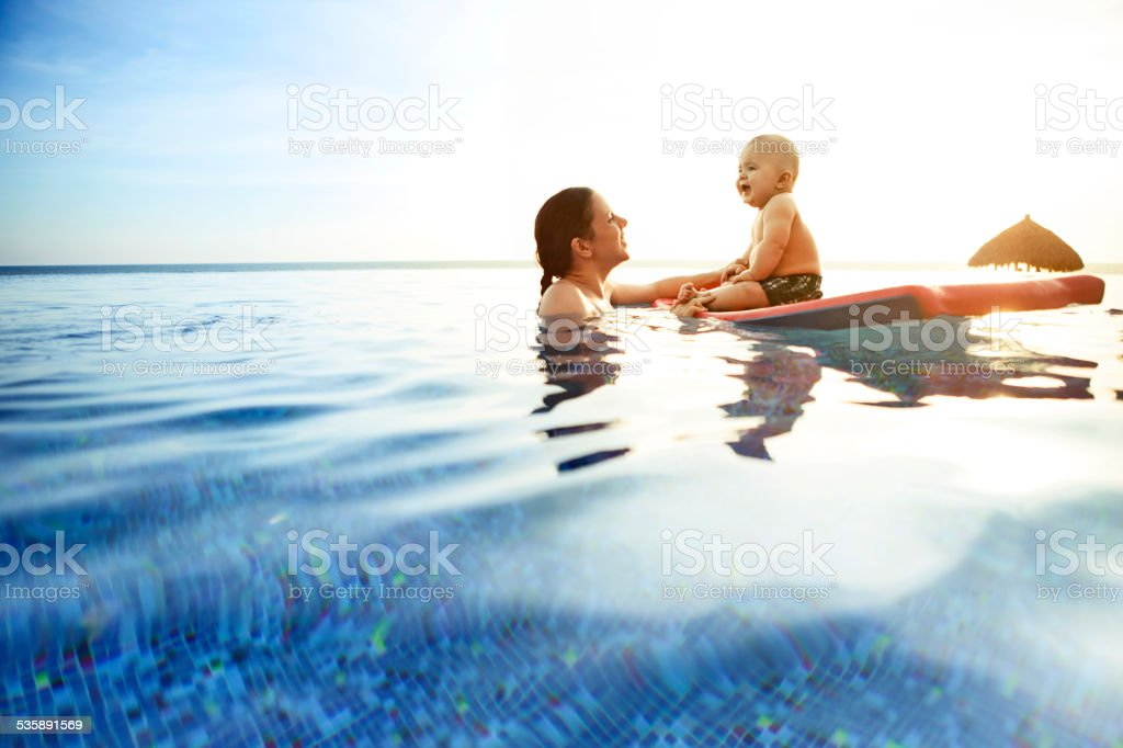 Child with mother in swimming pool stock photo