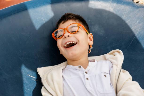 公園で大きなブランコで遊ぶ複数の障害を持つ子供。 - disabilitycollection ストックフォトと画像